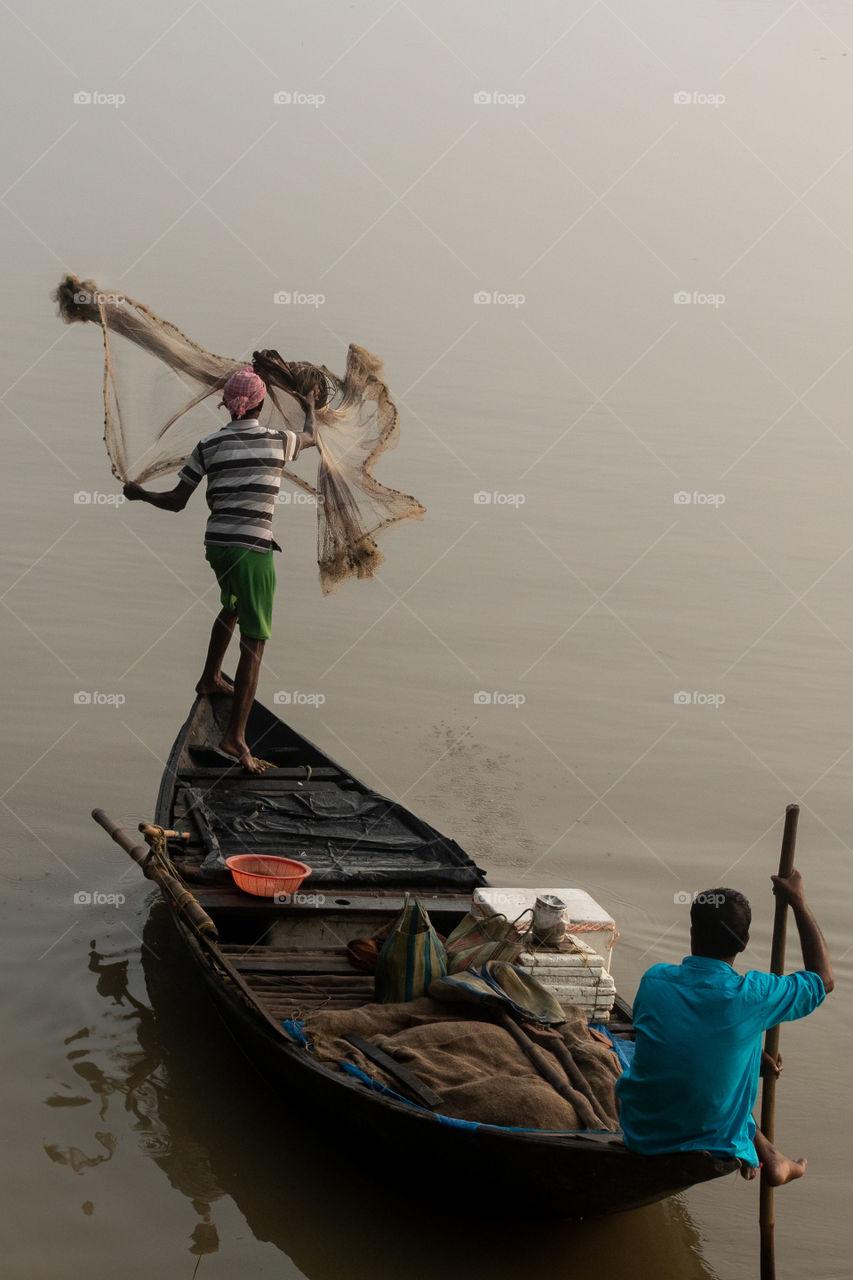 Fishermen is fishing with net.