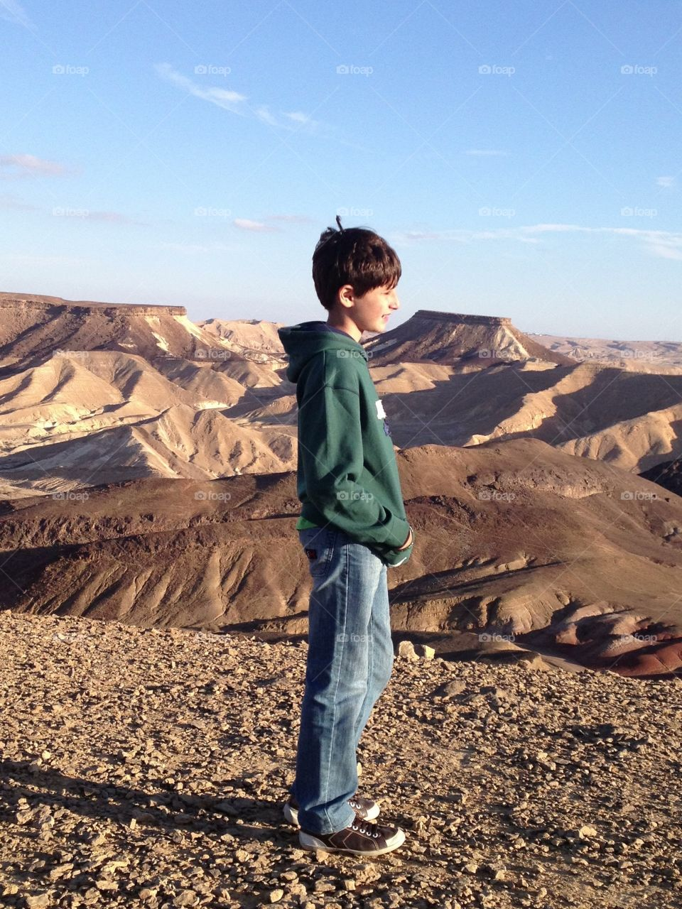 Smiling boy standing in desert