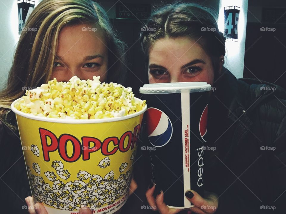 Female friends holding popcorn and soft drink in hand