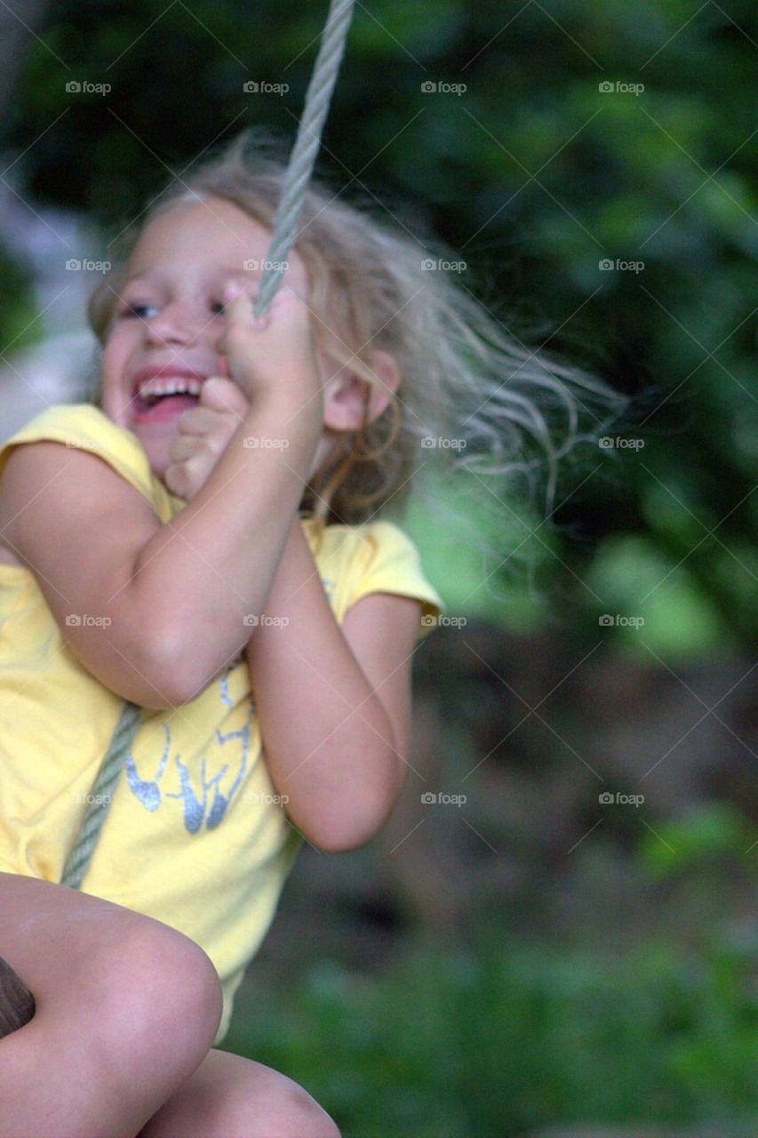 Girl enjoying on rope swing