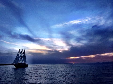Away into the night . Sail boat sails away in Santorini