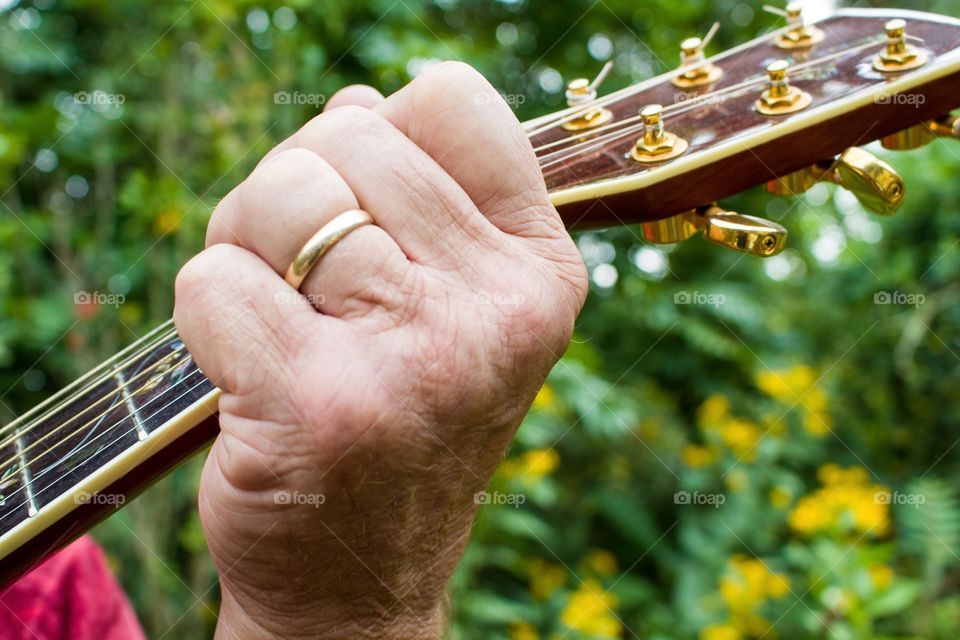 Close-up shot of an aging musician's hand on the neck of his guitar.