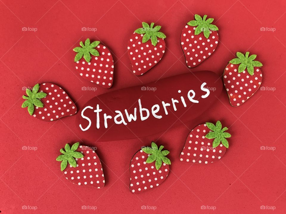 Strawberries conceptual composition with a stone and wooden objects over red background