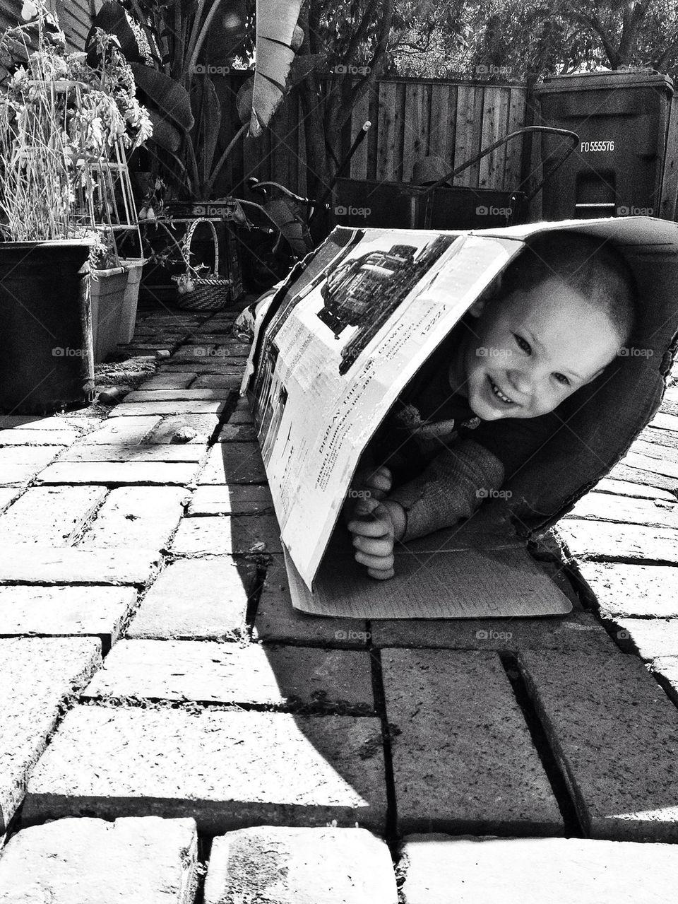 Boy joyfully playing in a cardboard box