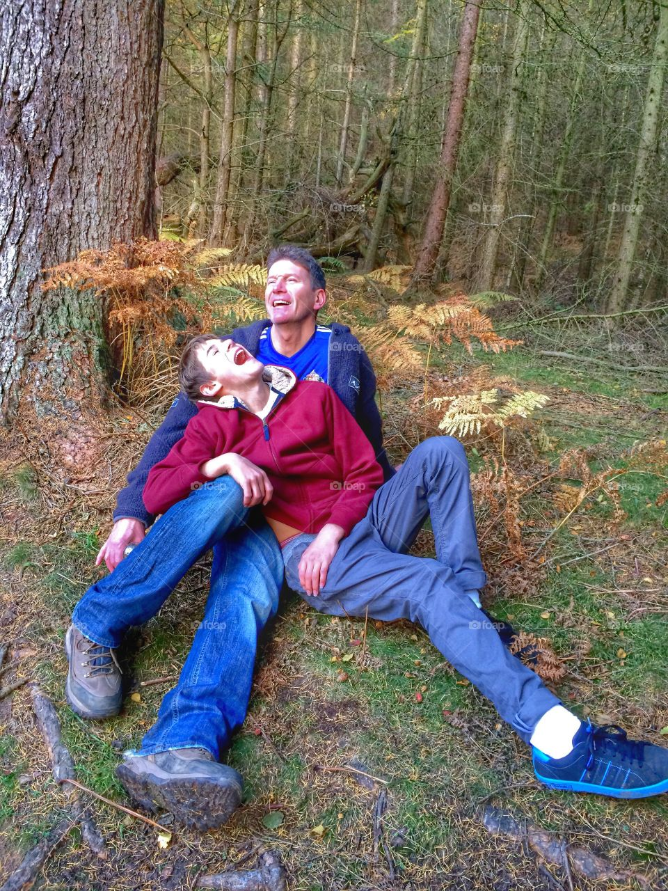 Close-up of happy father and son sitting on grass