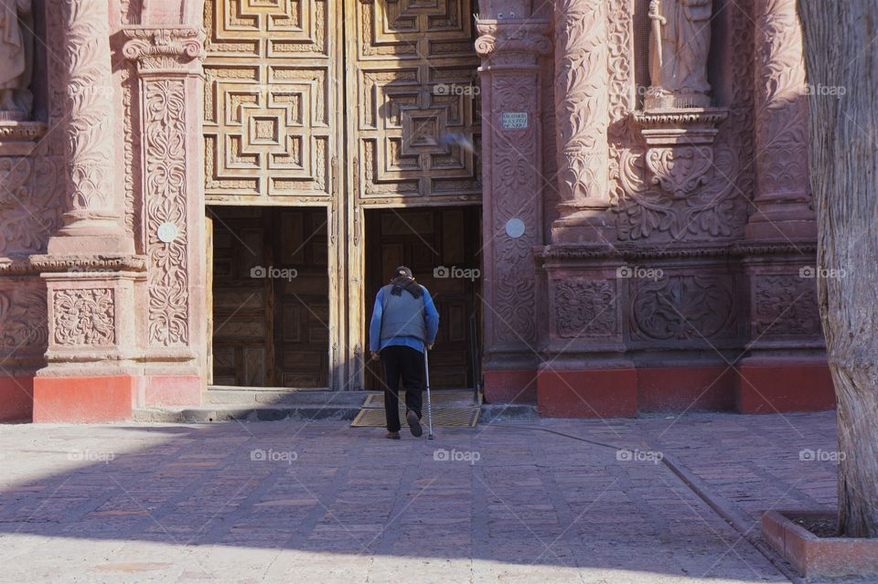 A man with cane is entering the doorway of a church in San Miguel de Allende, Mexico