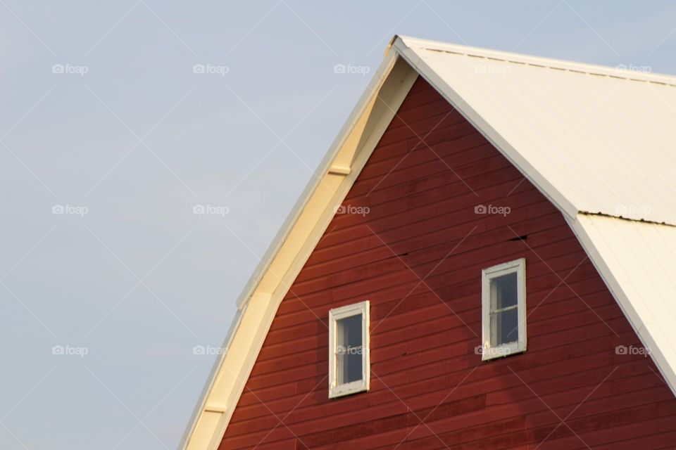 Isolated view of windows in the loft of a red barn against a clear sky
