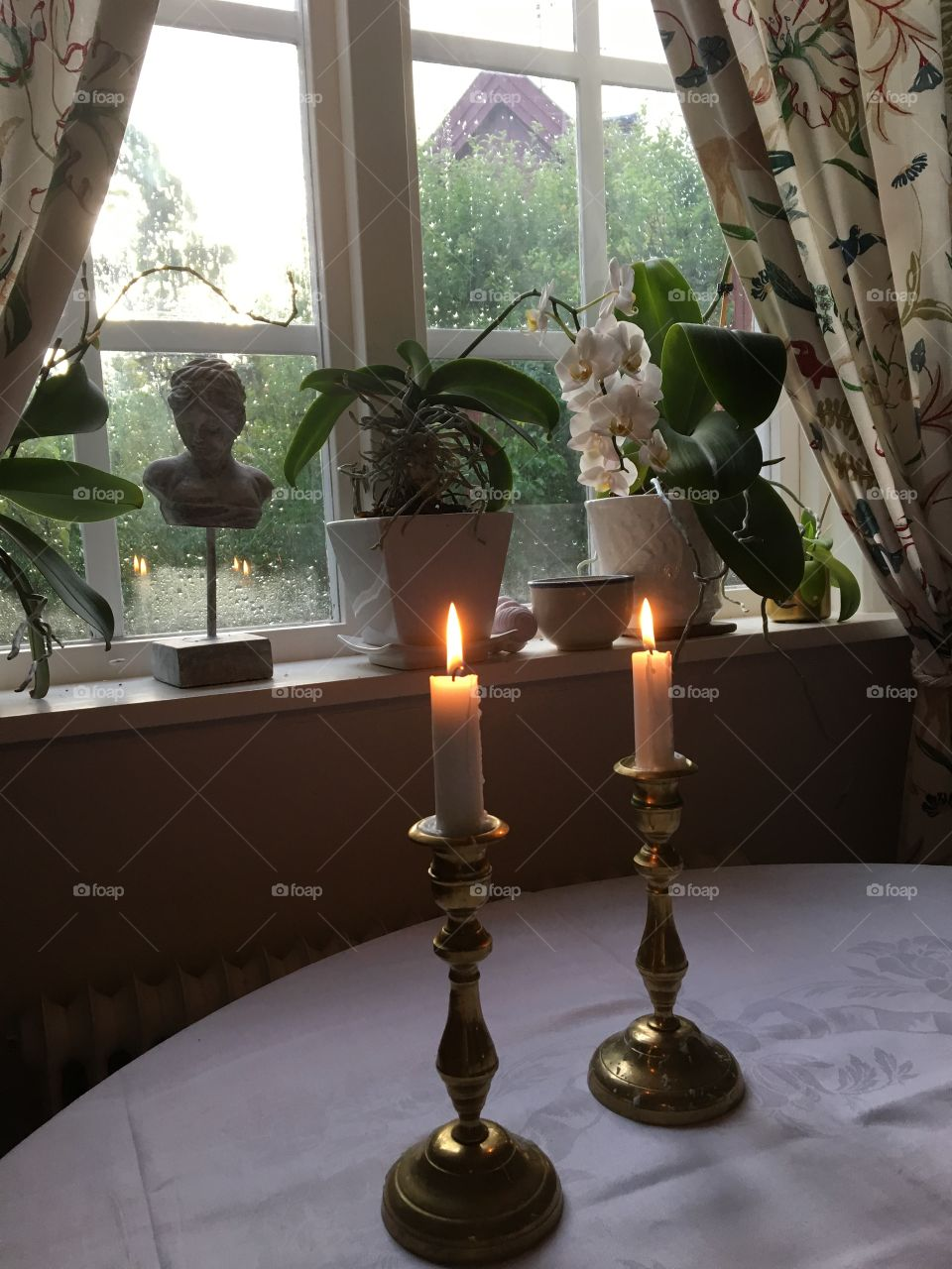 Candlelights and flowers  window with raindrops