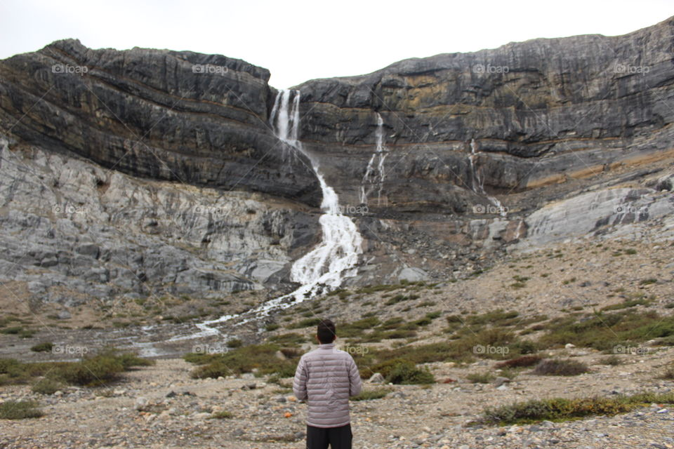 Guy standing next to a waterfall.