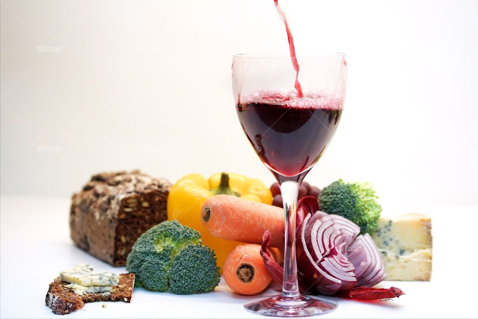 Vegetables and red wine over white background