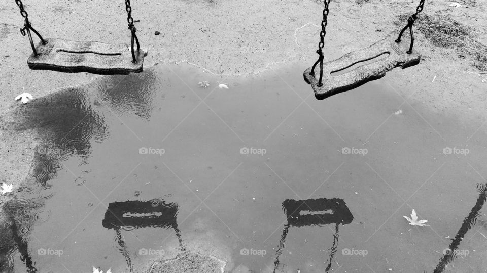 Reflection of children's swing in a puddle
