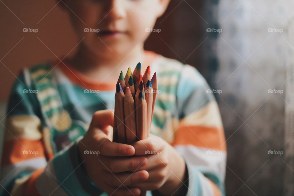 Close-up of hand holding colorful pencils