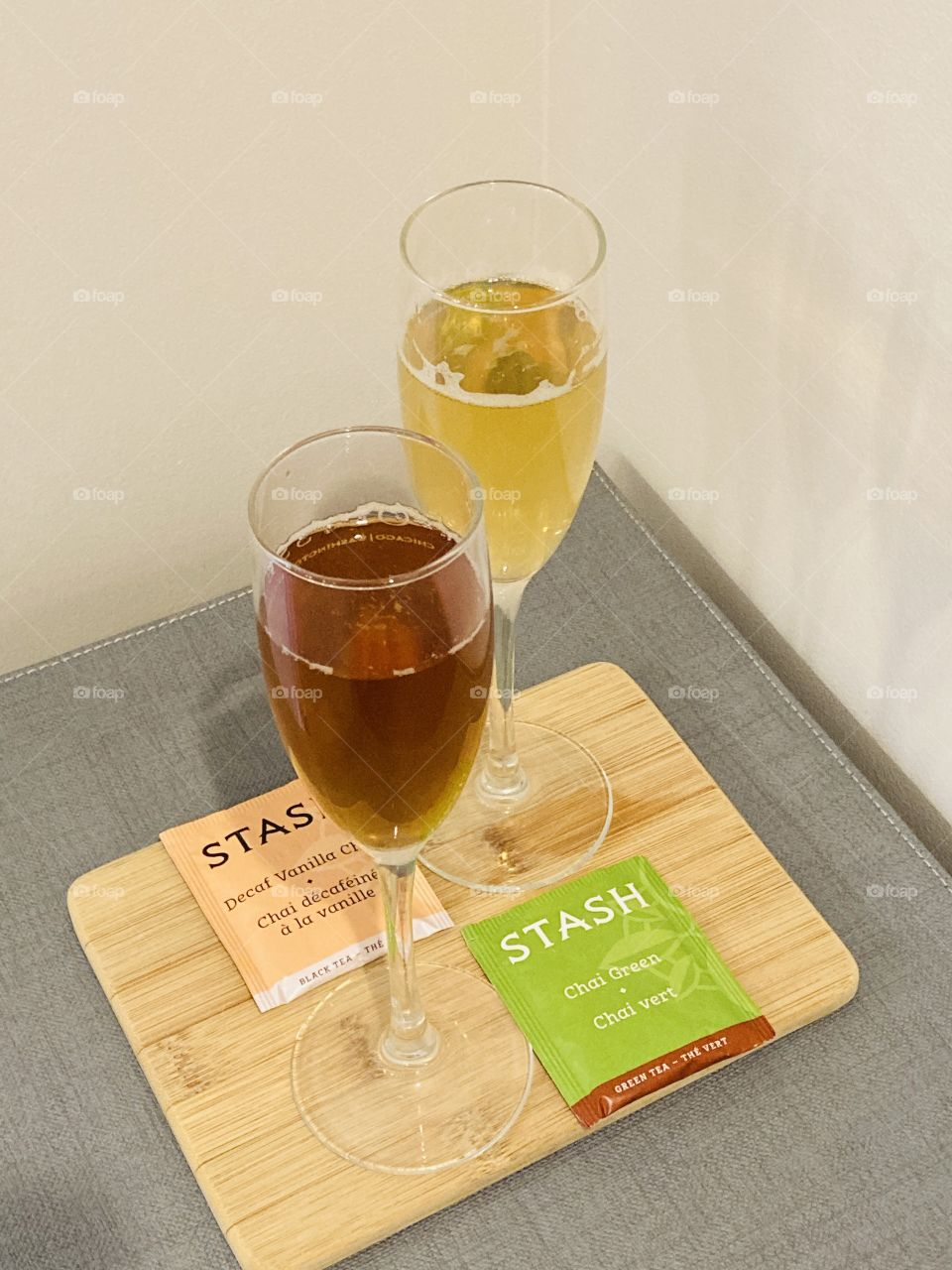 Bright pairing of Stash teas in champagne flutes with foil tea bags on a bamboo board