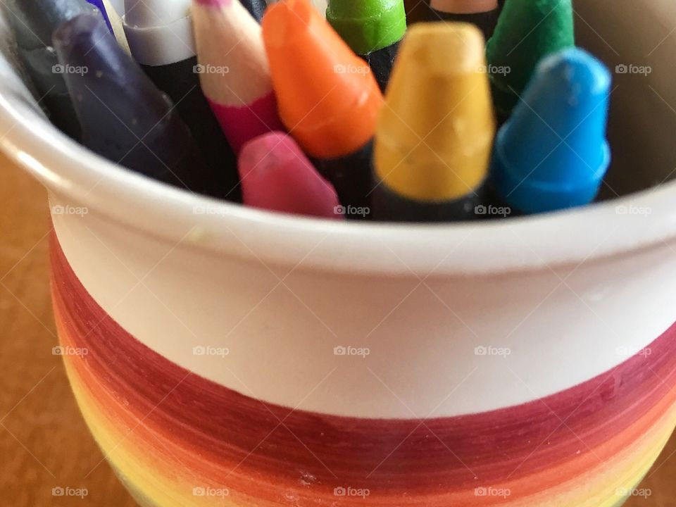 Art supplies of colourful crayons and pencils in rainbow ceramic pottery
