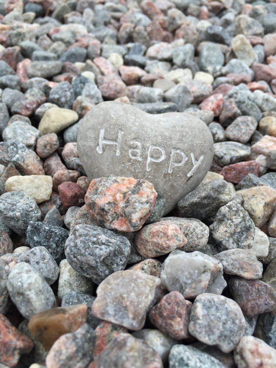 Happy text on heart shape rock