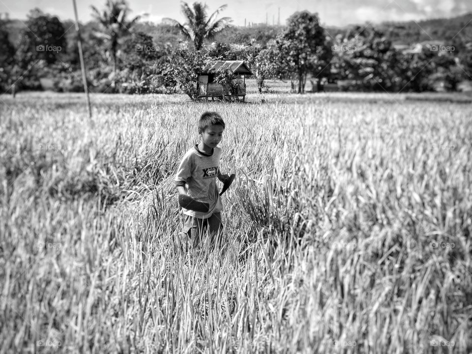 Boy holding flip-flops in hand at field