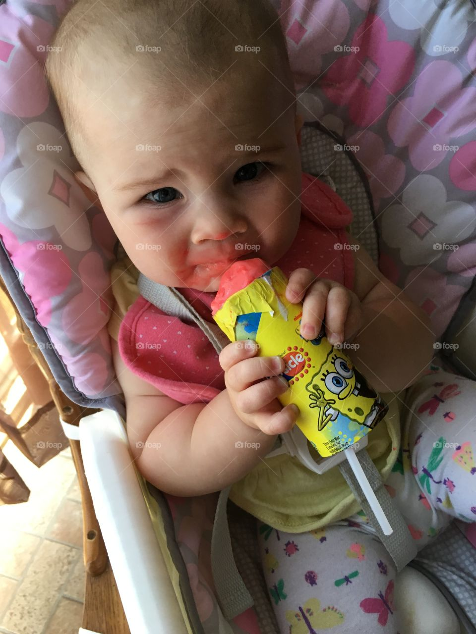 Elevated view of cute baby eating popsicles