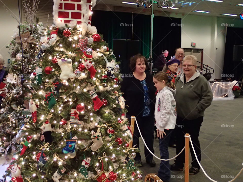 People enjoying some of the beautifully decorated Christmas trees at the annual Central Oregon Festival of Trees fundraising event during the holiday season.