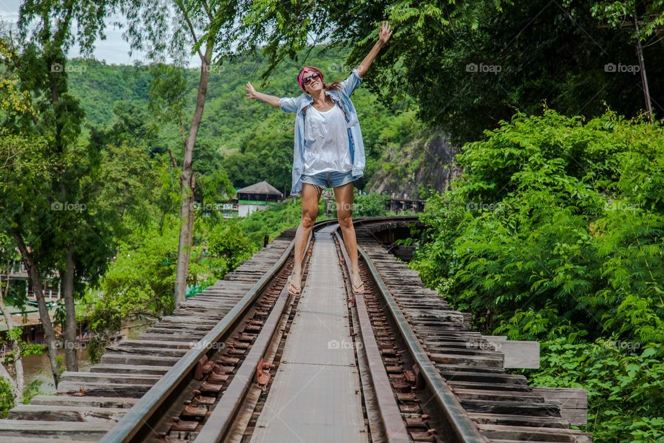 Happy woman standing on empty rail track