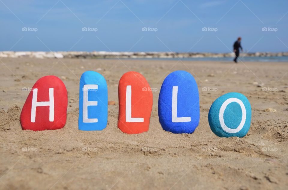 Hello on colourful stones with beach