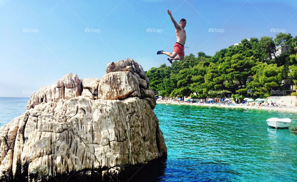 A man jumping off of a rock into clear waters