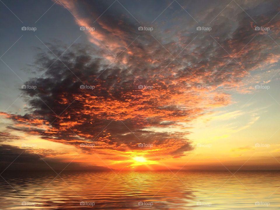 Spectacular orange sunset reflecting on a calm sea.