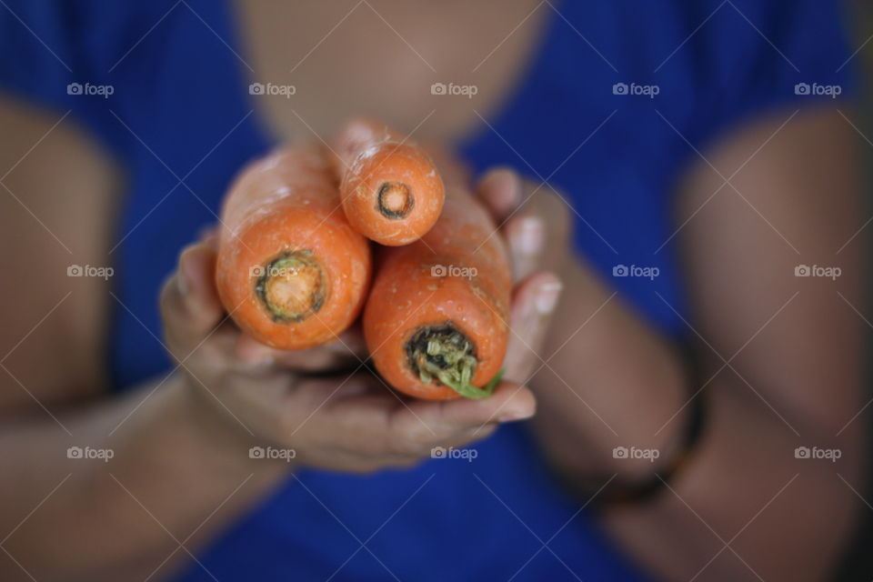 Mid section of girl holding carrots