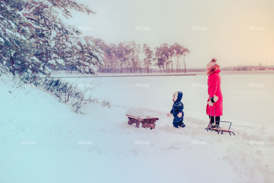 Mother and her little daughter are spending time together walking outdoors in forest in winter while snow falling. Woman is pulling sled, a few years old girl is walking through the deep snow, enjoying wintertime