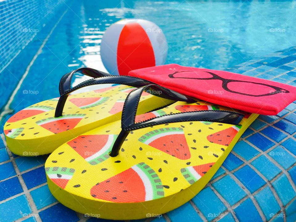 Flip flops with watermelons,pink sunglasses case and water ball near the pool
