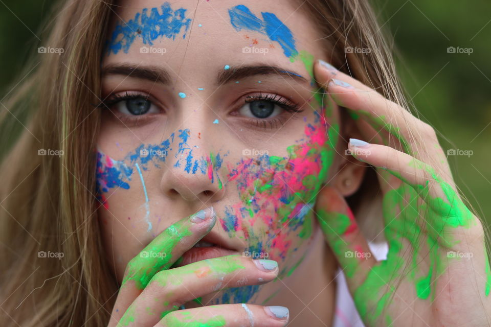 My daughter expressing her love of art and creativity. She splashed and brushed bright colorful paint on herself for her senior photo shoot.