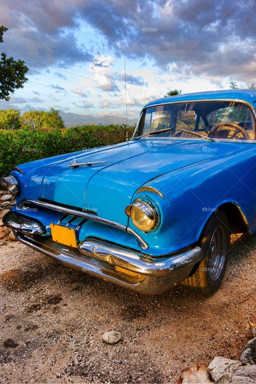Classic car in Trinidad, Cuba. Old blue American classic car at sunset time in mountainous and green outdoor setting in Trinidad, Cuba.