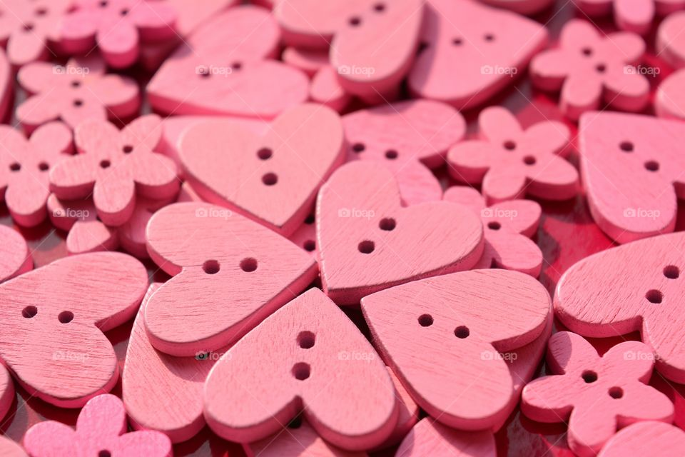 pink color wooden buttons hearts pink background