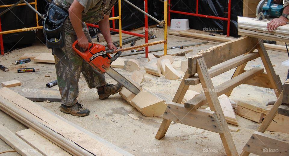 Man cutting wood using chain saw