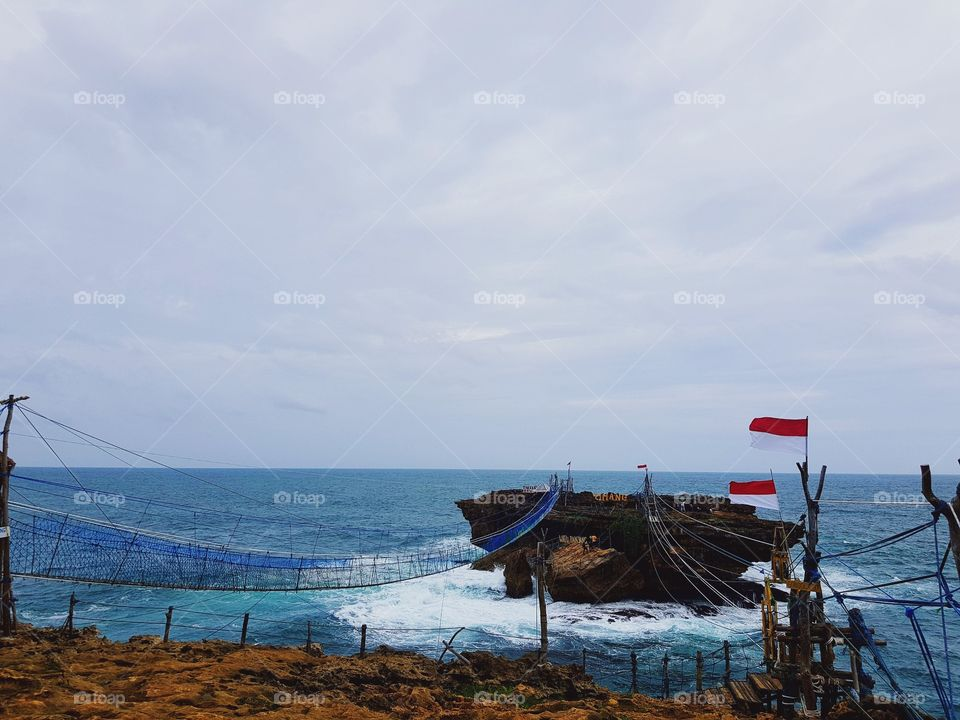This is Timang Beach, located in Gunung Kidul district, Yogyakarta, Indonesia.  Timang Beach not only presents the beauty of panoramic sea beach south that lies from the top of the cliff wall, but this beach turned out to present an attraction that can spur our adrenaline.  A traditional gondola made of wooden chains and driven by a mechanical system from the mine's tugs will lead us across to the island in the middle of the ocean. The distance is not far, only about 50 meters, but the distance becomes so thrilling when we are already on the Gondola to cross to the next island.  The road to this place.  The rocky and slippery roads require you to be careful. I suggest if you are in doubt it is better to enter by using offroad car. Because the road is quite dangerous. can-can your car tire broke if not careful. I recommend not to use motorcycle matic. But from the difficulty of this field everything will be paid off with a very beautiful and beautiful scenery.