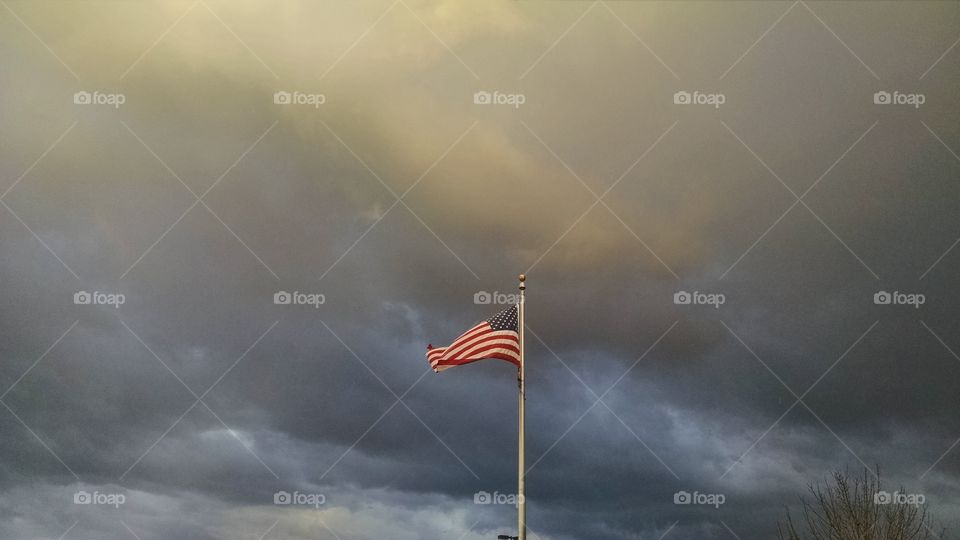 American flag with stormy sky