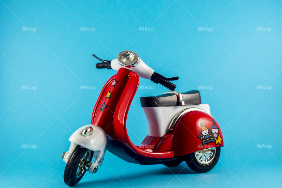 Red toy motorcycle on the blue background