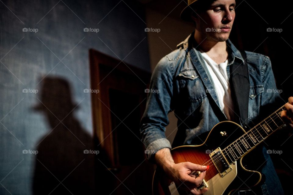 Guy wearing hat playing guitar in a recording studio. Rock and roll guitar player wearing denim with blue walls