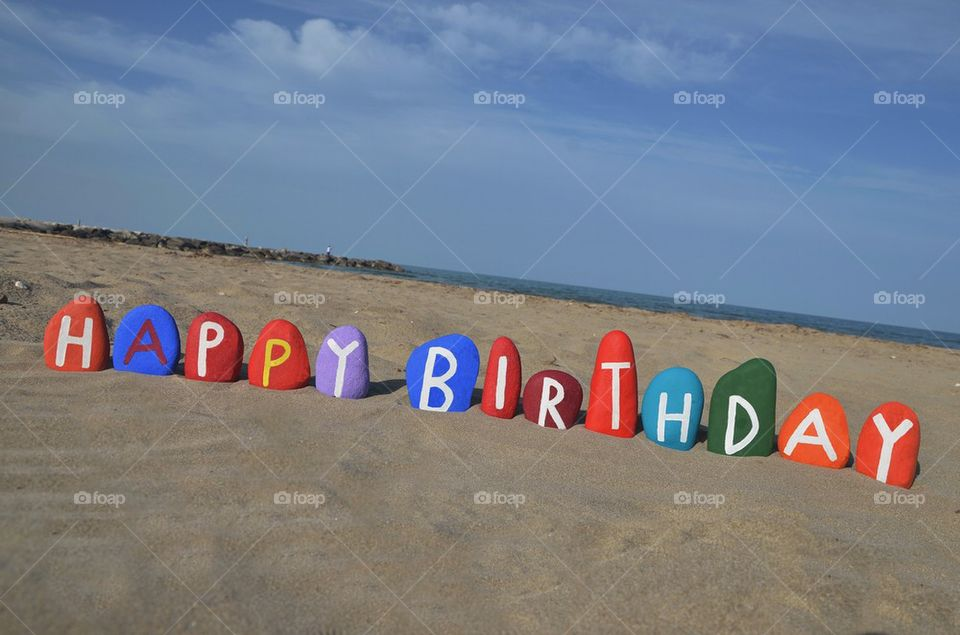 Happy Birthday on colourful stones over the sand