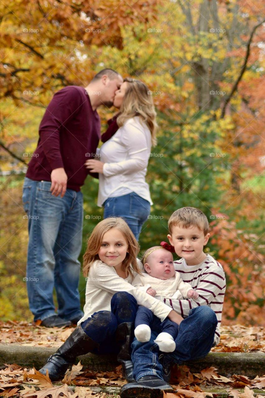 Children sitting in front of parents kissing